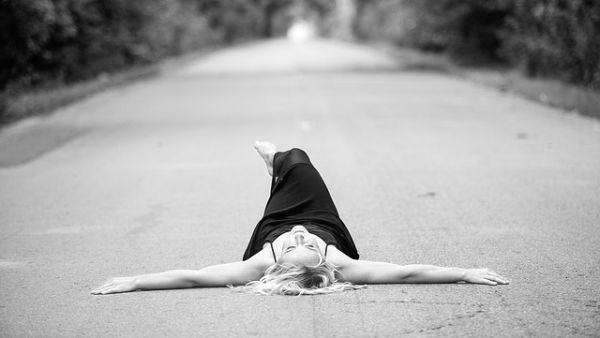 道路に寝転ぶ女性 自由 開放感